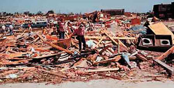 Grand Island residents in the South Loust area sort through piles of wreckage on June 4, 1980. Starr Elementary can be seen in the background. A few apartments (far right) survived the storm.